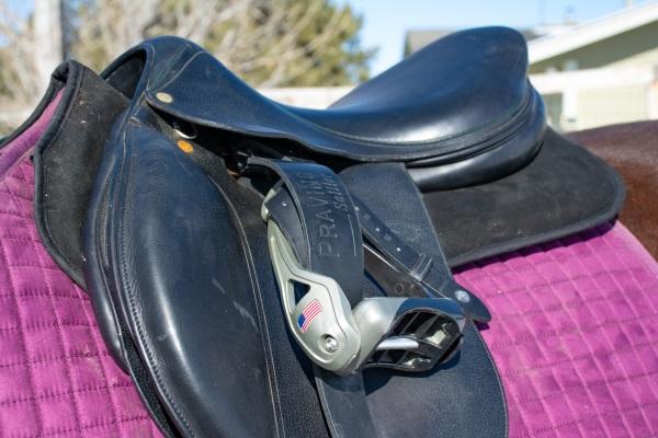 a black saddle on a half pad and purple pad