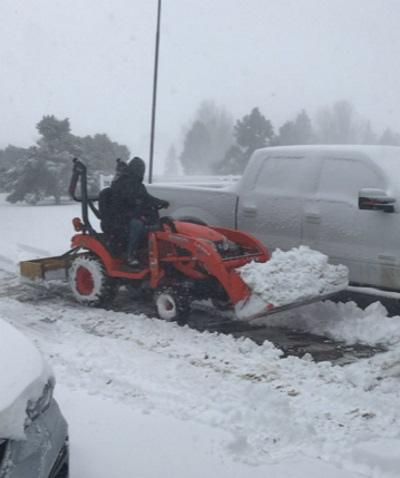 a man clearing snow with a tractor