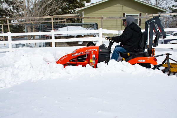 a man clearing snow with a small tractor