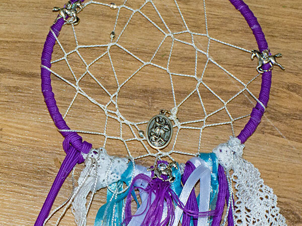 close up view of a homemade dream catcher with horse charms