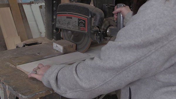 a person using a radial arm saw to cut wood
