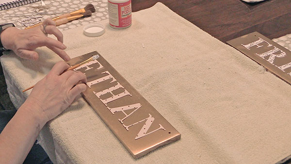 gluing letters onto a piece of wood to make a stall sign for a horses stall