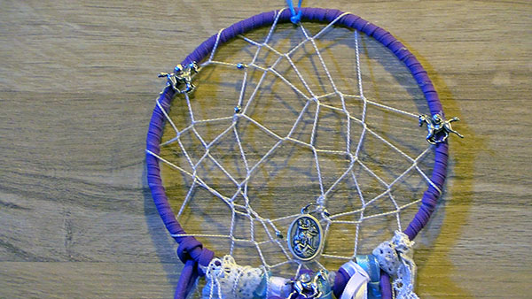 close up view of the dream catcher when it is hanging on a wall