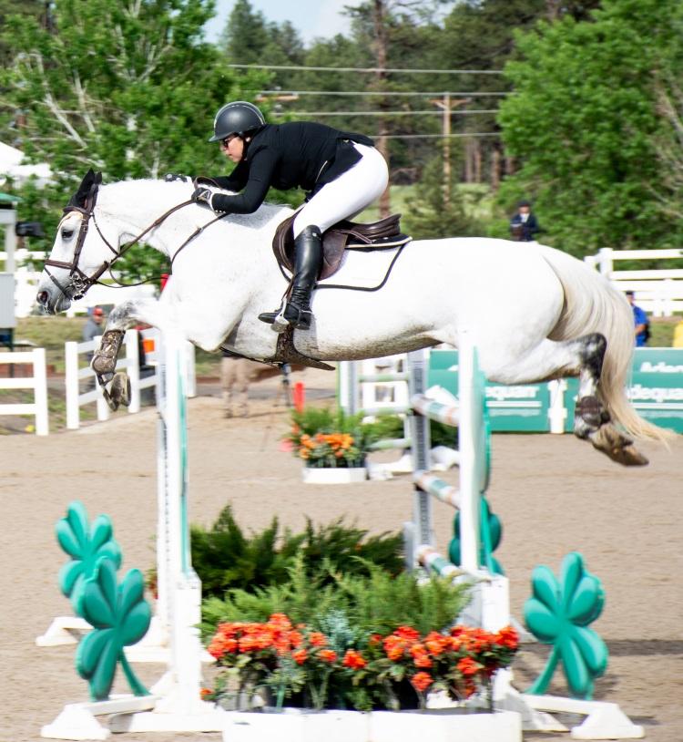 a horse jumping a big jump at a grand prix