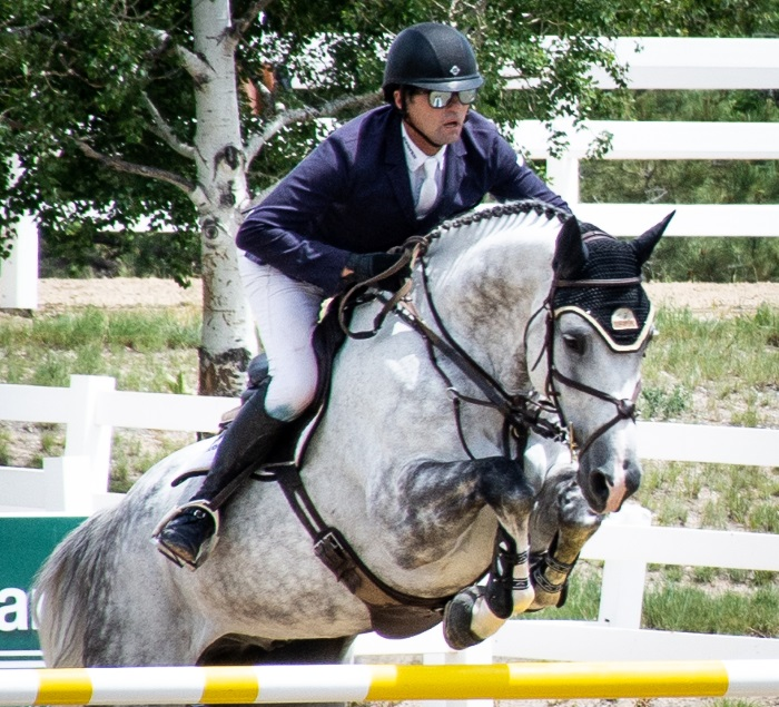 a horse and rider going over a jump