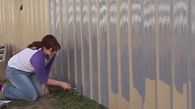 painting the bottom edge of a metal barn