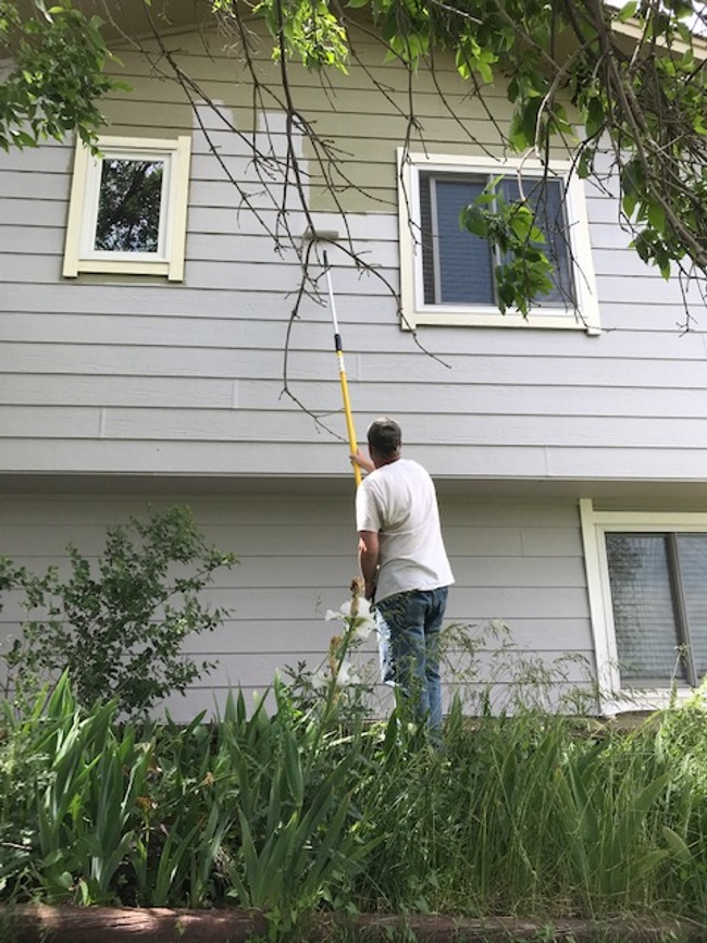 using a pole extender to paint a tall house